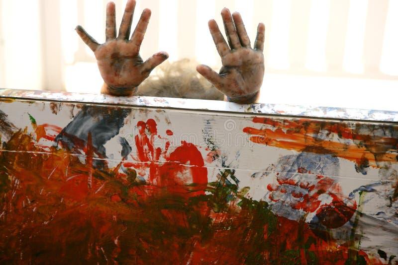 De kunstenaarshanden die van kinderen multikleuren schilderen stock foto's