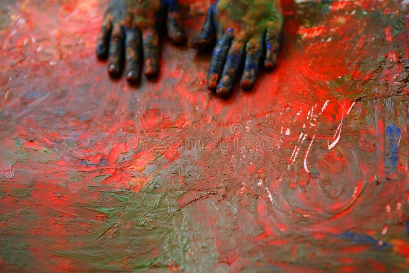 De kunstenaarshanden die van kinderen multikleuren schilderen stock afbeeldingen