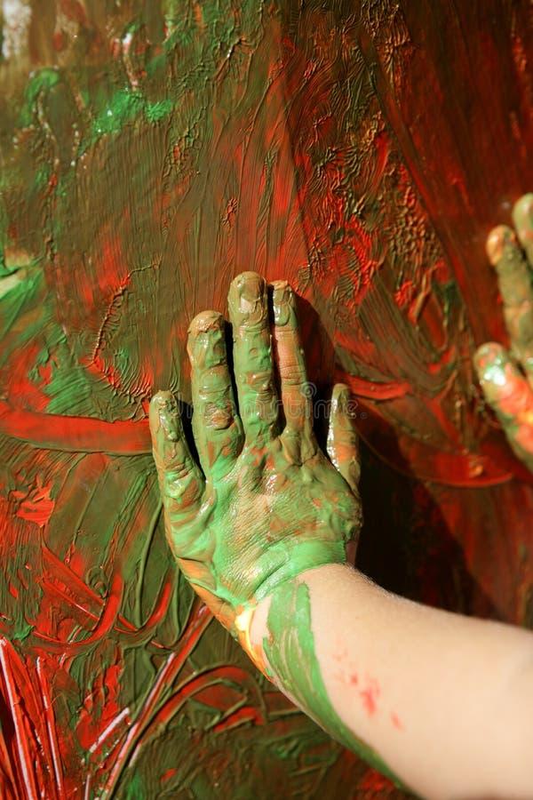 De kunstenaarshanden die van kinderen multikleuren schilderen stock foto