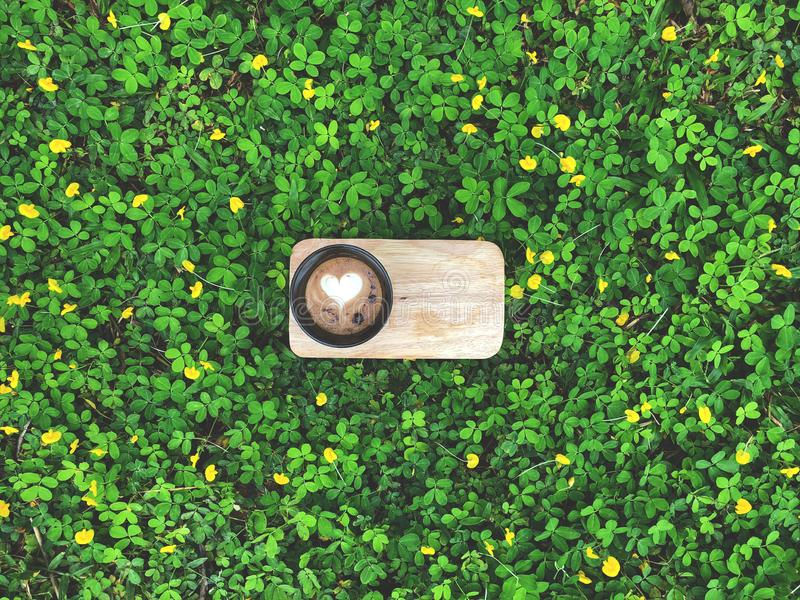 De kunstkoffie van Latte van het liefdehart in zwarte kop op houten dienblad met groene bladeren en weinig gele bloem stock foto