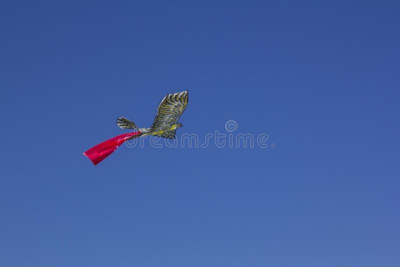 De kunstmatige vogel stijgt in de blauwe hemel Een vogel vormde vliegervliegen door de lucht stock fotografie