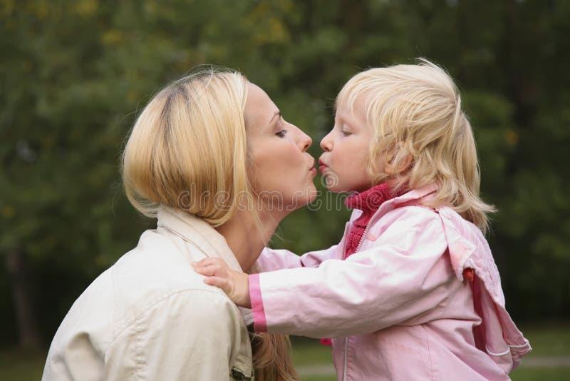 De kus van het meisje en van de moeder stock afbeelding