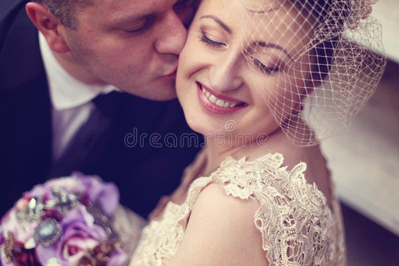 De kussende bruid van de bruidegom royalty-vrije stock afbeeldingen