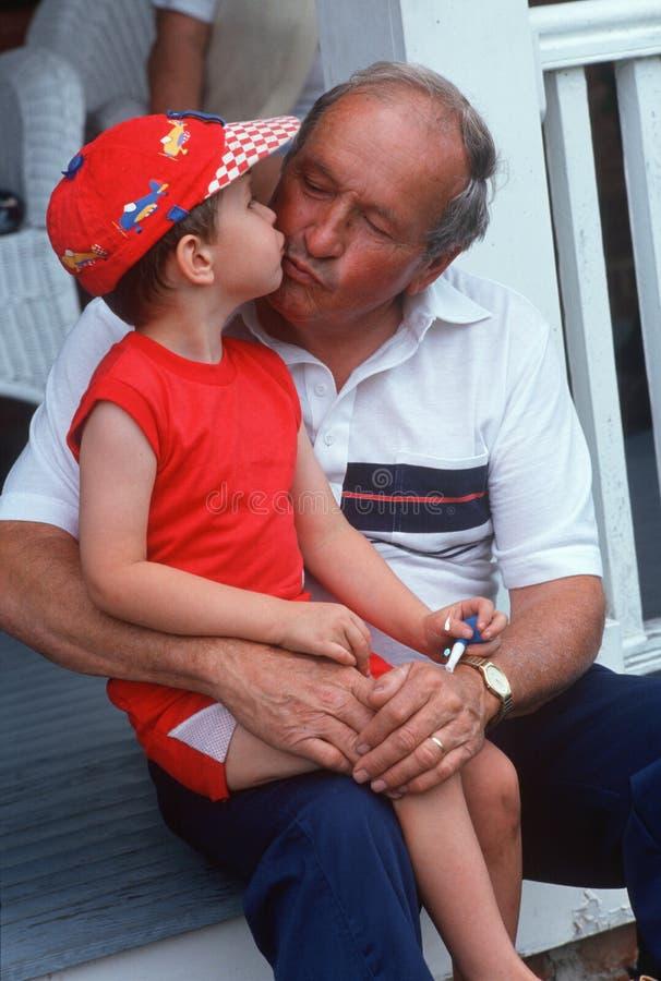 De kussende kleinzoon van de grootvader op portiek royalty-vrije stock foto