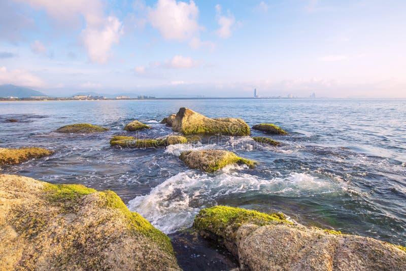 De kust en de rooskleurige wolken bij zonsopgang royalty-vrije stock foto