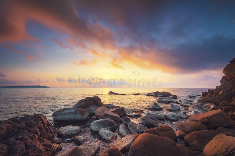 De kust en de rooskleurige wolken bij zonsopgang royalty-vrije stock afbeeldingen