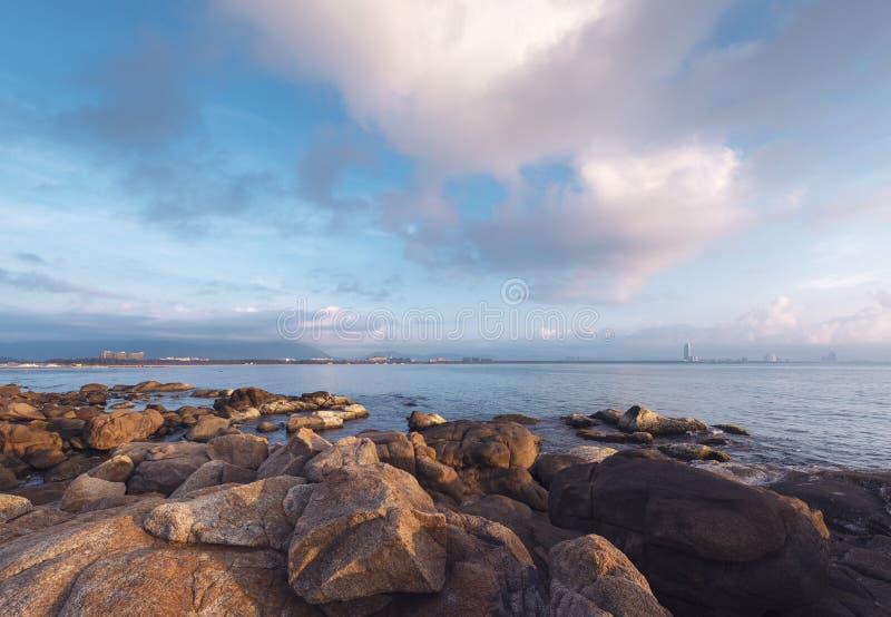 De kust en de rooskleurige wolken bij zonsopgang royalty-vrije stock afbeelding