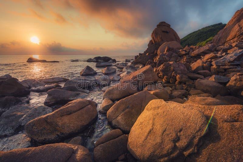 De kust en de rooskleurige wolken bij zonsopgang stock foto