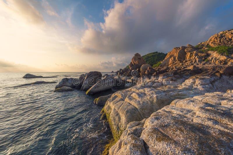 De kust en de rooskleurige wolken bij zonsopgang stock afbeelding