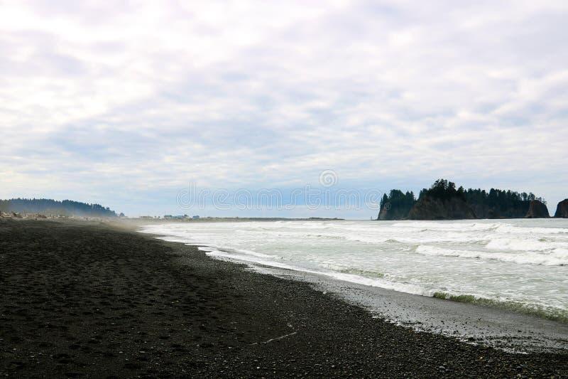 De kust van de Vreedzame Oceaan in de vroege mistige ochtend op de achtergrond van rotsen stock foto