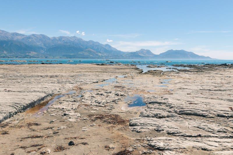 De kustlijn met rots voegt dichtbij Kaikoura in Nieuw Zeeland samen royalty-vrije stock foto