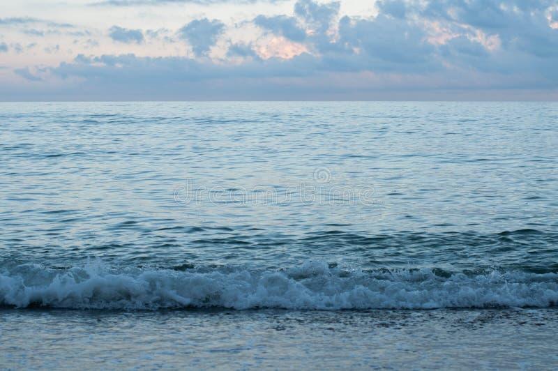 De kustlijn van de de zomerschemer in blauwe zonsondergangavond stock afbeeldingen