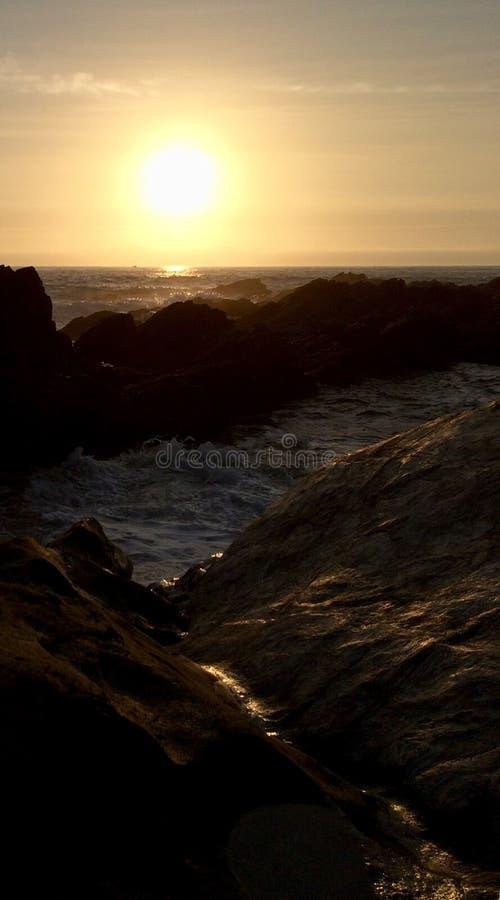 De kustrotsen van het zonsondergangsilhouet met golven stock afbeeldingen
