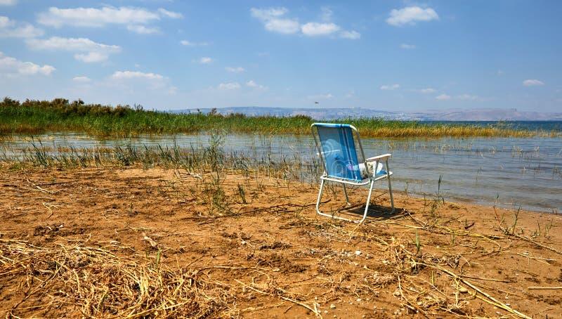 De kuststrook van het Kinneretmeer met struiken en een eenzame bevindende stoel Juli stock afbeelding