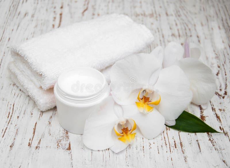 De kuuroordhoofdzaak roomt witte handdoeken en orchideeën af stock afbeeldingen
