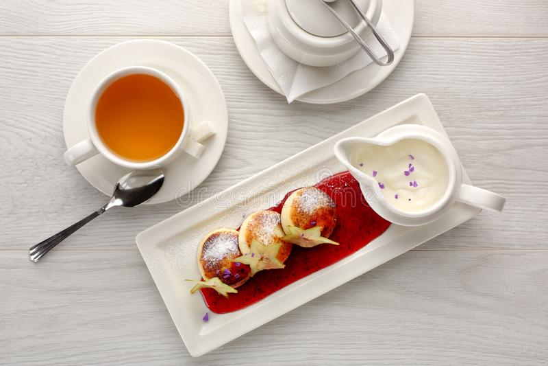 De kwarkpannekoeken met aardbei blokkeren, zure room op witte houten achtergrond, ontbijt of lunch, thee royalty-vrije stock afbeelding