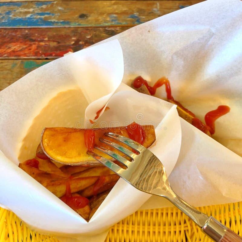 De läckra potatischiperna, med ketchup på den arkivfoton