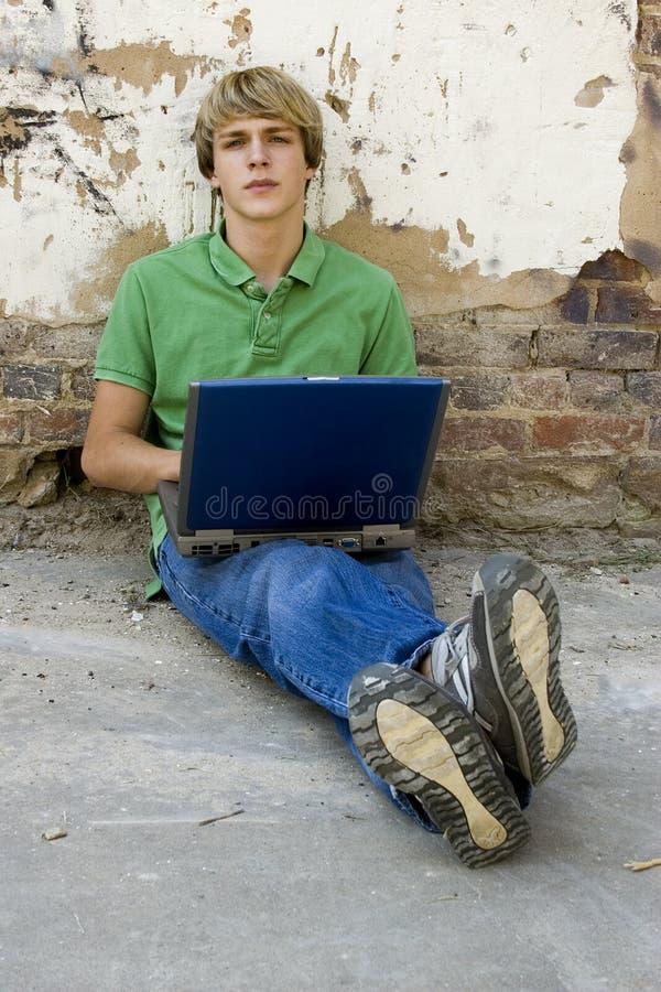 De l'adolescence avec l'ordinateur portatif images stock