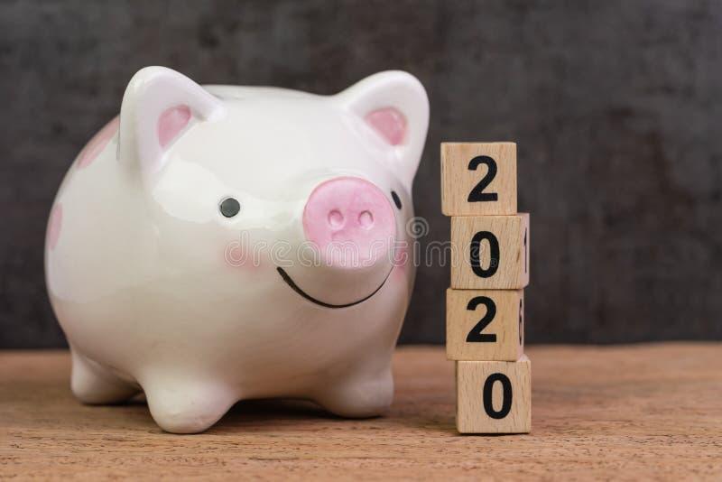 But de l'année 2020, épargne, budget ou investissement financier, tirelire rose de sourire heureuse avec la pile de blocs en bois image stock