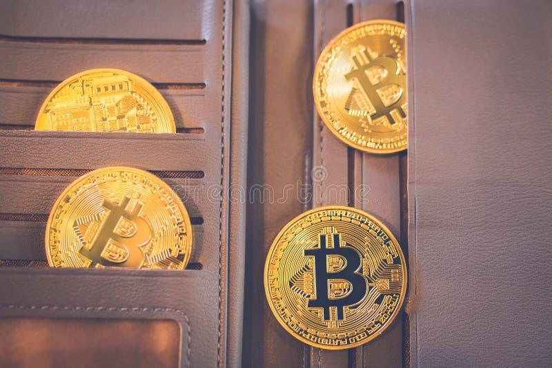 De l'or de Bitcoin est situé dans un portefeuille en cuir brun photo stock