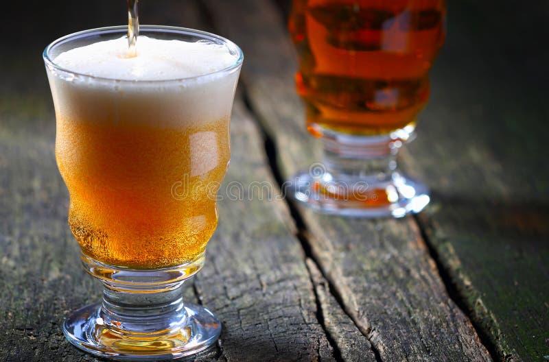 De la bière est versée avec la couronne de mousse photo libre de droits