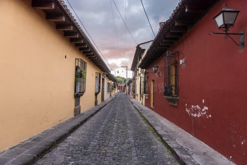 De la calle centro de la ciudad vacío adentro de Antigua, Guatemala Antigua es una pequeña ciudad rodeada por los volcanes en Gua imágenes de archivo libres de regalías