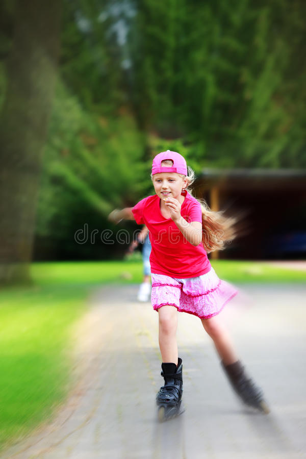 De la chica joven falta de definición radial patinadora en línea de la diversión al aire libre fotos de archivo libres de regalías