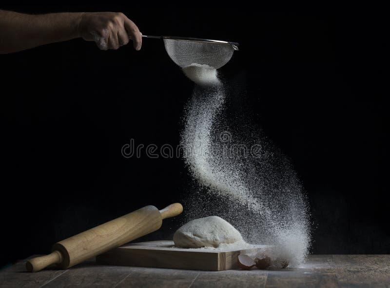 De la farine est arrosée au-dessus d'une boule de pâte sur un conseil en bois avec r photos stock