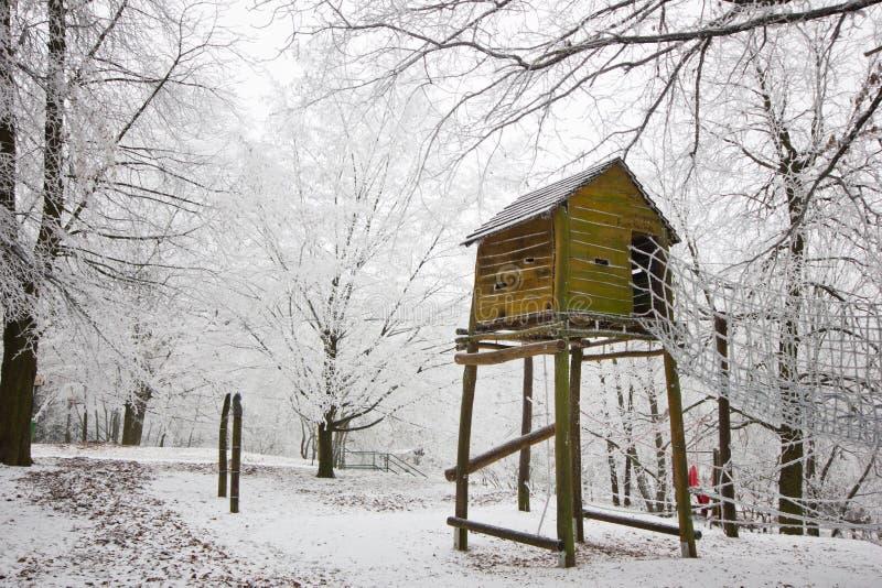 De la loge couverte de neige en bois et d'enfants du ` s sur un arbre photos libres de droits