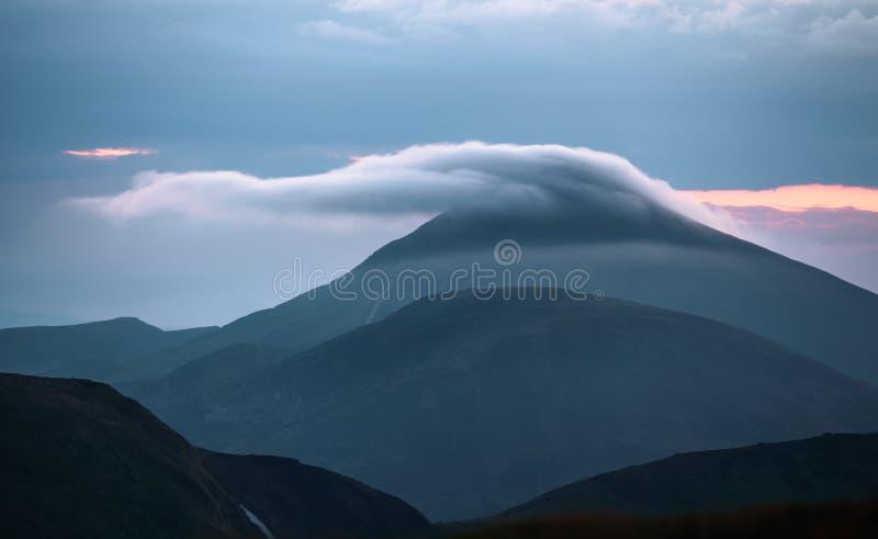 De la montaña el valle abre la escena de fascinación con la puesta del sol Alta montaña con un pico en la niebla fotos de archivo libres de regalías