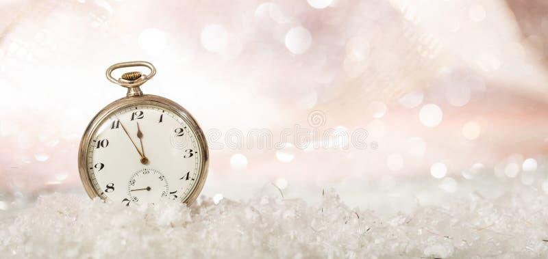 De la Noche Vieja la celebración del partido Minutos a la medianoche en un reloj de bolsillo pasado de moda, fondo nevoso del bok fotografía de archivo libre de regalías