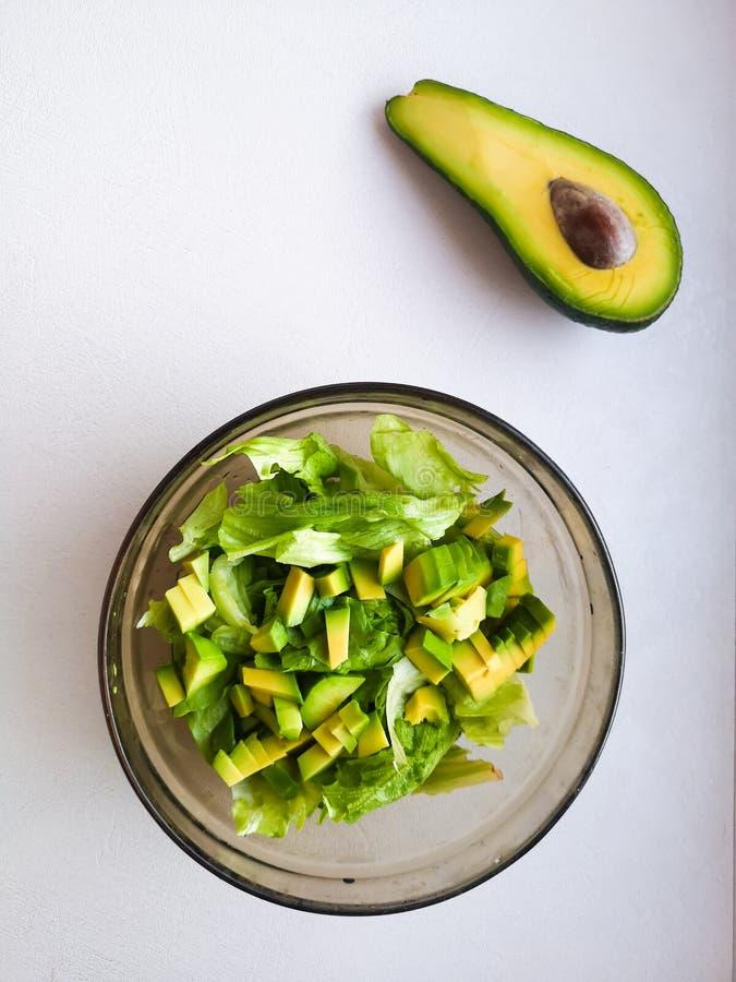 De la salade avec l'avocat et les graines de sésame, huile est versée, sur un en bois Salade d'avocat dans un plat, nourriture vé photos libres de droits
