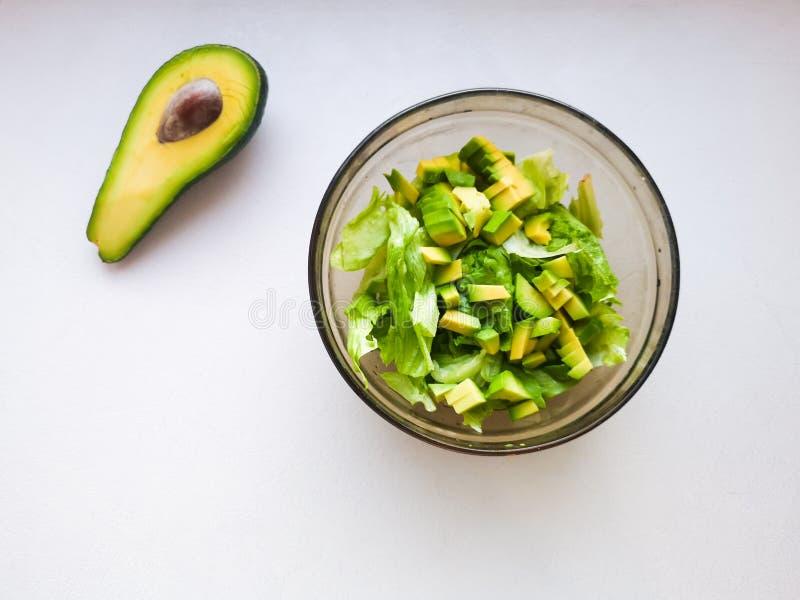 De la salade avec l'avocat et les graines de sésame, huile est versée, sur un en bois Salade d'avocat dans un plat, nourriture vé photo stock