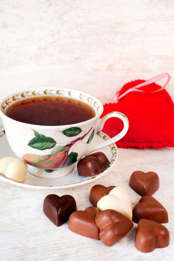 De la tarjeta del día de San Valentín del ` s del día del té todavía del tiempo vida con los chocolates en forma de corazón imagen de archivo libre de regalías