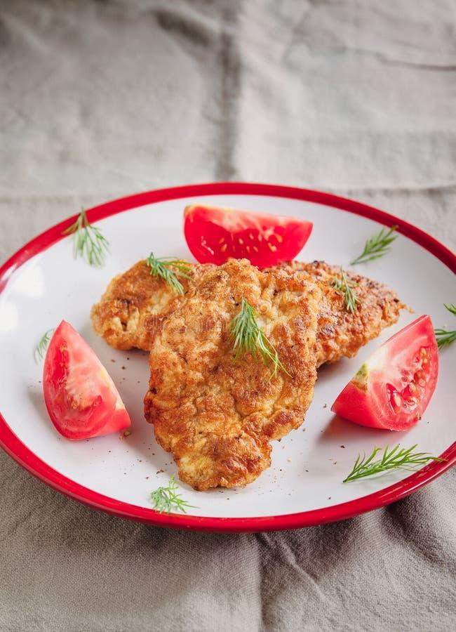 de la viande juteuse, des côtelettes de poulet et des tomates sur une assiette blanche sur un simple fond de lin clair servi avec photographie stock