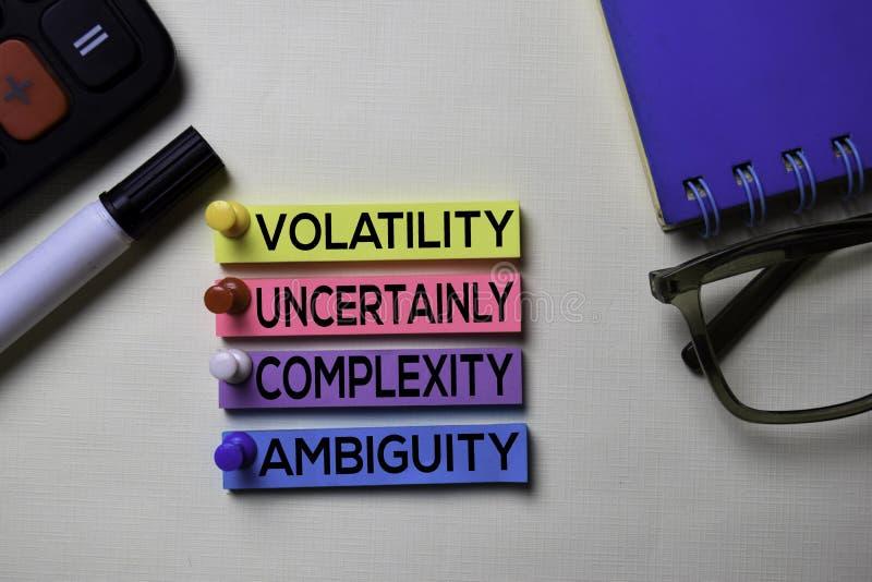 De la volatilidad ambigüedad de la complejidad incierto - texto de VUCA en las notas pegajosas aisladas en el escritorio de ofici imagenes de archivo