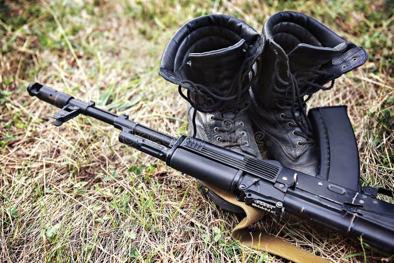 De laarzen van de militairenkel en een het geweerclose-up van de Kalashnikovaanval royalty-vrije stock foto's