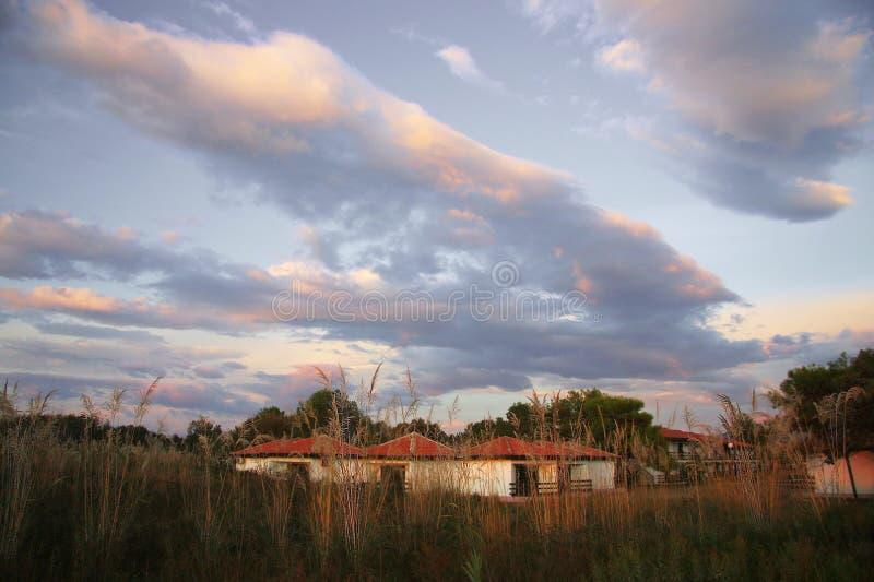De laatste straal van de zon verlicht de mooie wolken en de witte huizen stock afbeeldingen