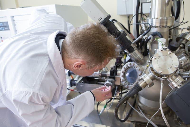 De laboratoriumspecialist onderzoekt de verkregen gegevens over een speciaal apparaat om steekproeven te analyseren stock afbeeldingen