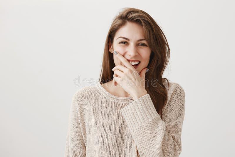 De lach verhoogt levensduur Studio van positieve jonge vrouw met bruin haar wordt geschoten die en mond behandelen met hand grinn royalty-vrije stock fotografie