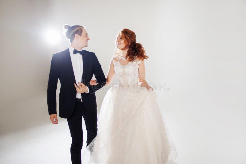 De lachende bruid en de bruidegom bekijken elkaar, dansen en springen met gehuwd geluk, stock afbeelding