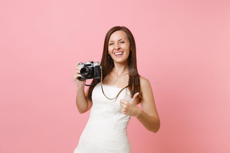 De lachende bruidvrouw in witte huwelijkskleding die duim tonen houdt retro uitstekende fotocamera tegen, kiezend personeel royalty-vrije stock fotografie