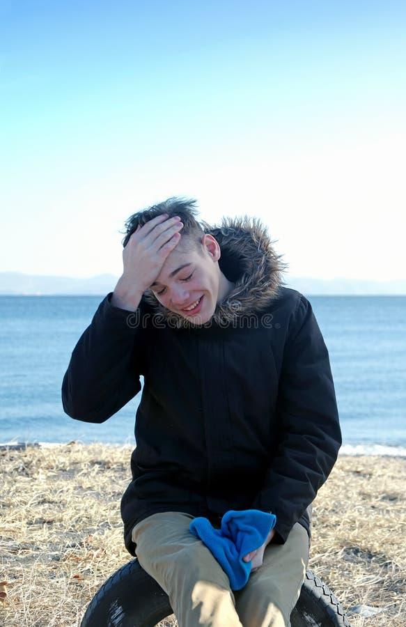 De lachende jongen zit in overzees stock afbeeldingen