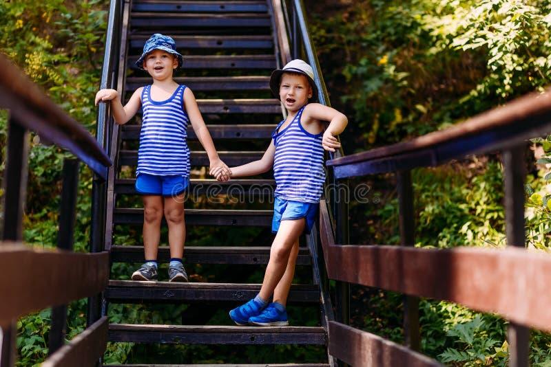 De lachende kinderen in gestreepte t-shirts en blauwe borrels bevinden zich houdend handen op de stappen in de zomer stock fotografie