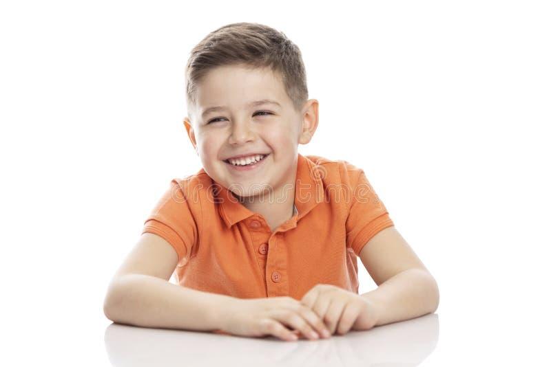 De lachende school-age jongen in een heldere oranje polot-shirt zit bij een lijst Close-up Isolirvoan op een witte achtergrond royalty-vrije stock fotografie