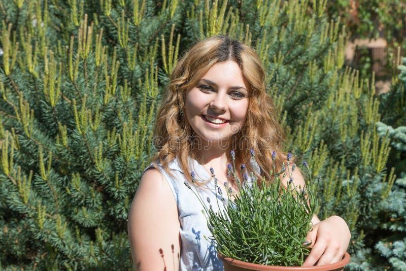 De lachende tiener die een bloempot met lavendel houden royalty-vrije stock fotografie