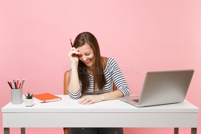 De lachende vrouw met verminderd hoofdholdingspotlood die op hand leunen zit, werkt bij wit bureau met eigentijdse PC-laptop royalty-vrije stock afbeeldingen