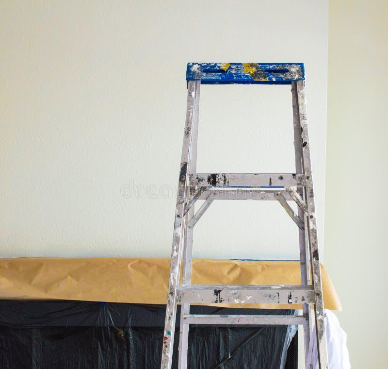 De ladder van de aluminiumschilder voor een open haard die met plastiek en document wordt behandeld royalty-vrije stock foto