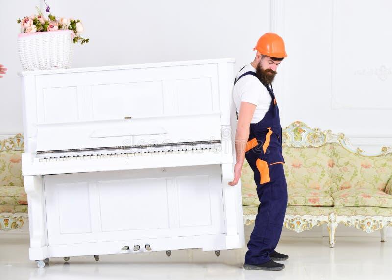 De lader beweegt pianoinstrument Zware ladingenconcept Mens met baard omhoog arbeider in helm en overallliften, inspanningen aan stock foto's