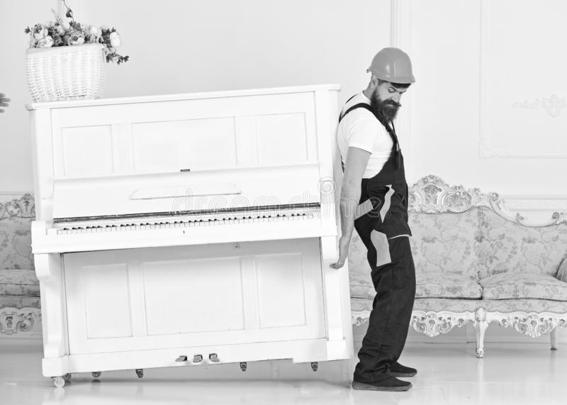 De lader beweegt pianoinstrument Zware ladingenconcept Mens met baard omhoog arbeider in helm en overallliften, inspanningen aan royalty-vrije stock afbeelding